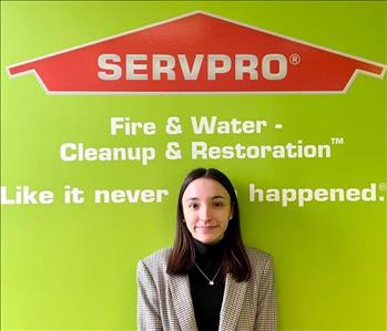 Female employee smiling with Servpro background
